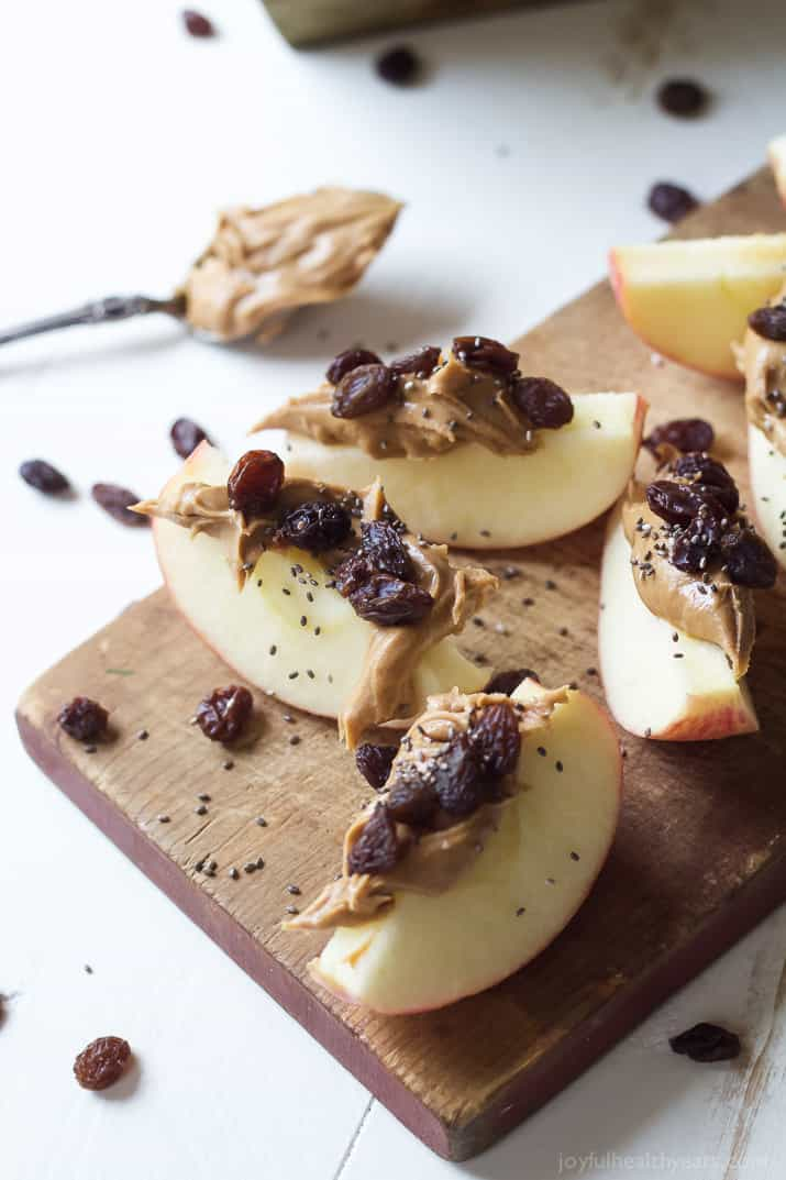Overhead view of apple wedges with peanut butter, dried cranberries and chia seeds on a wooden cutting board