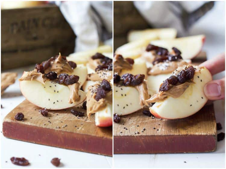 Apple wedges with peanut butter, dried cranberries and chia seeds on a wooden cutting board