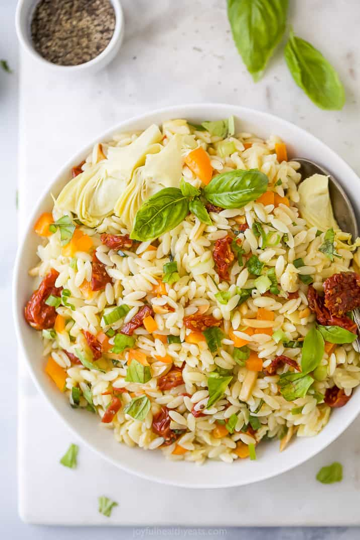 A White Bowl Filled with Mediterranean Pasta Salad on a Placemat