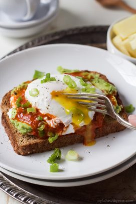 A piece of Harissa Avocado Toast Topped with Poached Egg with a fork cutting into the egg.