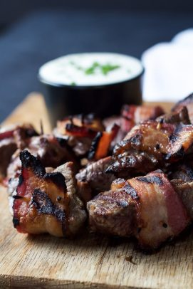 Bacon Wrapped Tenderloin Bites on a wooden board with Creamy Horseradish Sauce