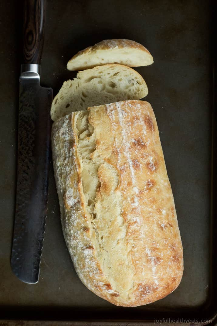 A loaf of cursty Italian Bread with a couple slices cut