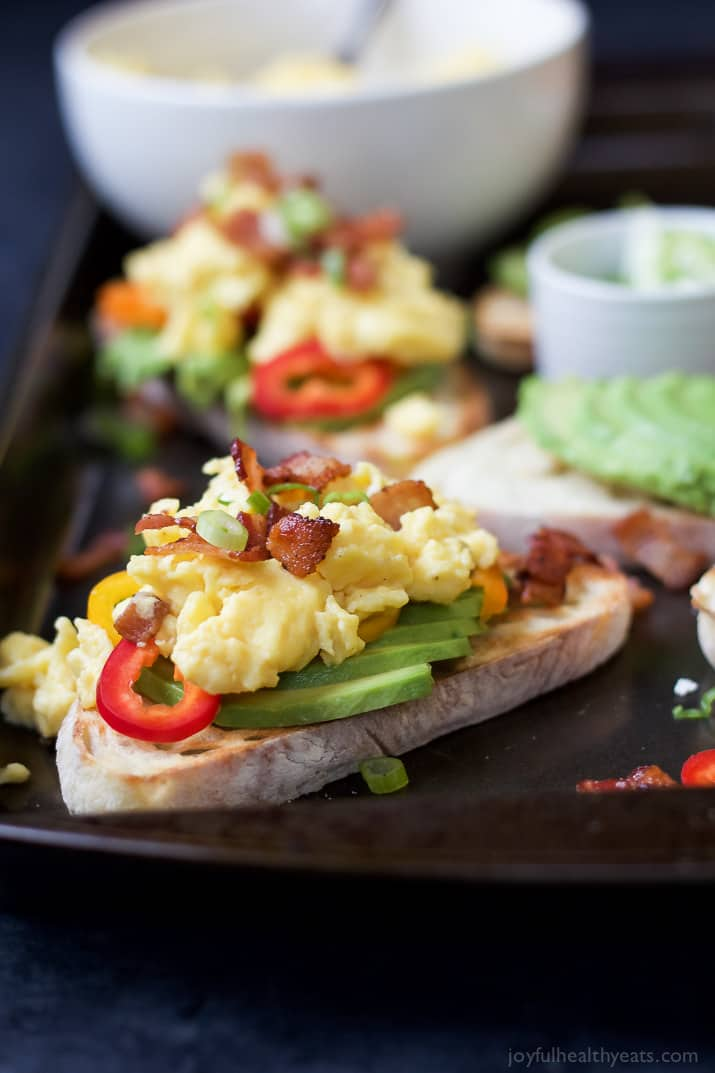 Breakfast Bruschetta topped with scrambled eggs, salty bacon, sweet peppers, all on a creamy Avocado Toast! These are so stinking good! The perfect Saturday morning breakfast or brunch recipe. | joyfulhealthyeats.com