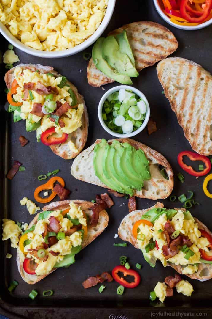 Slices of Avocado Toast topped with Breakfast Bruschetta including scrambled eggs, bacon, scallions and pepper slices