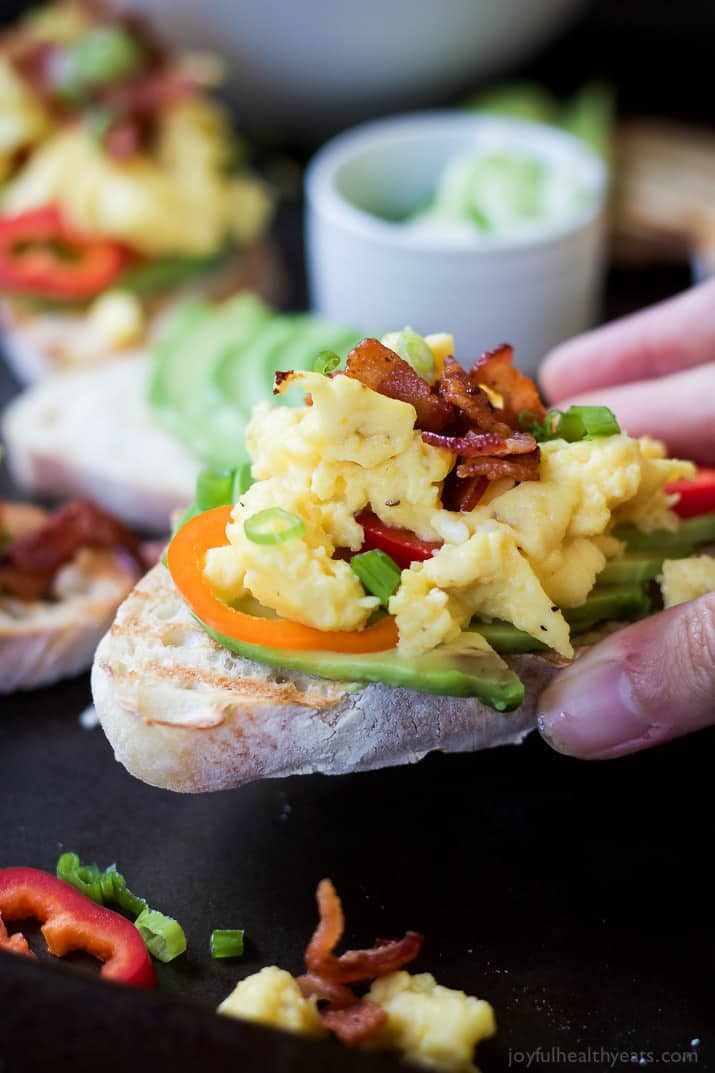 Breakfast Bruschetta of Avocado Toast topped with scrambled eggs, bacon, scallions and pepper slices