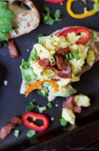 Breakfast Bruschetta topped with scrambled eggs, salty bacon, sweet peppers, all on a creamy Avocado Toast! These are so stinking good! The perfect Saturday morning breakfast or brunch recipe. | joyfulhealthyeats.com Easy Healthy Recipes