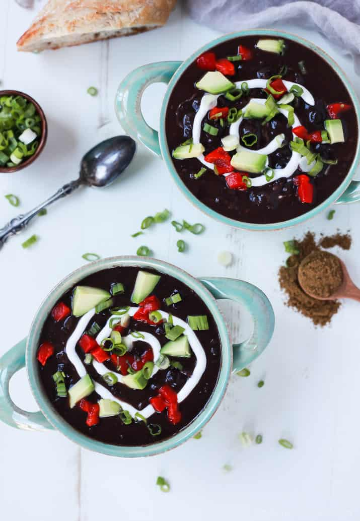 Top view of two bowls of Black Bean Soup topped with diced peppers, avocado, scallions and a swirl of sour cream