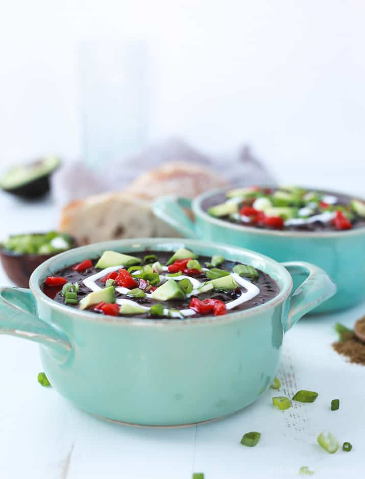 Two crocks of Black Bean Soup topped with diced peppers, avocado, and scallions