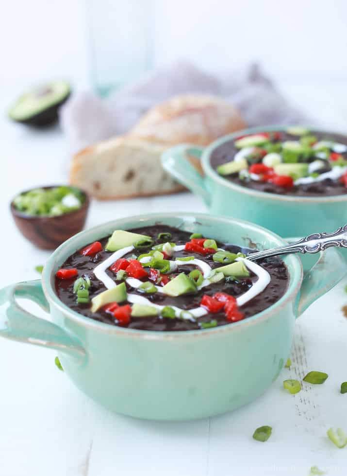 Close up view of a bowl of Black Bean Soup with diced peppers, avocado, scallions, and a swirl of sour cream