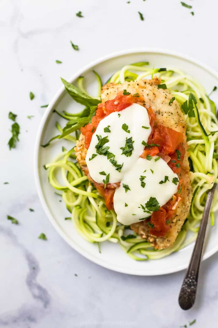 baked chicken parmesan on a bed of zucchini noodles