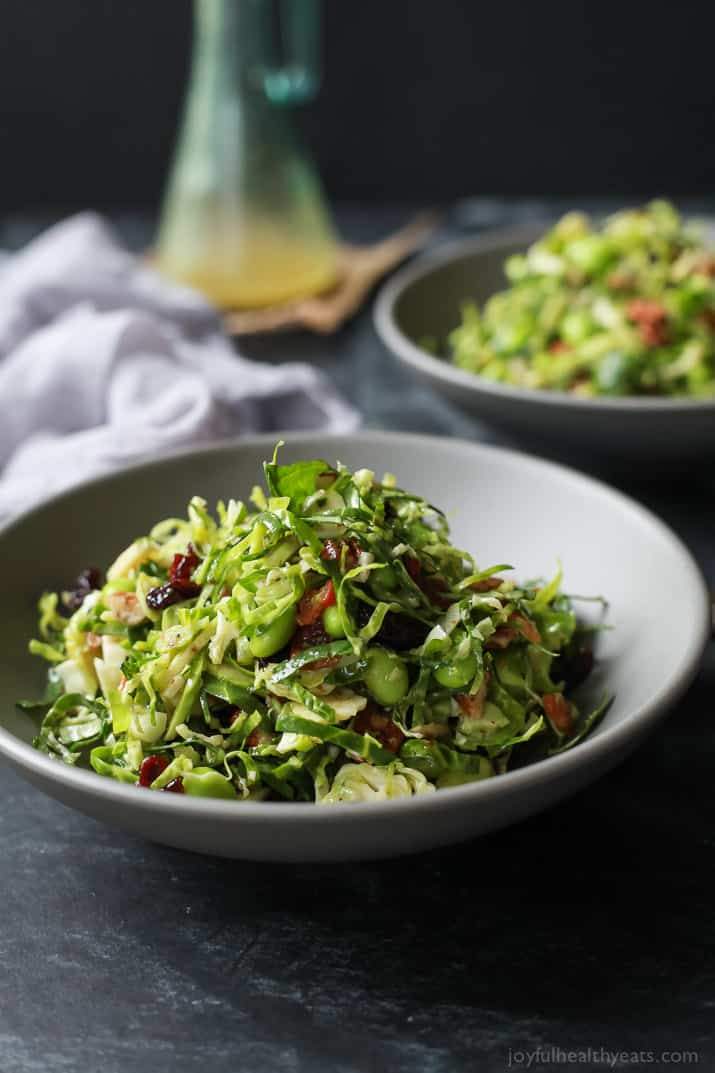 Autumn Kale & Shaved Brussel Sprout Salad with bacon and edamame in a bowl