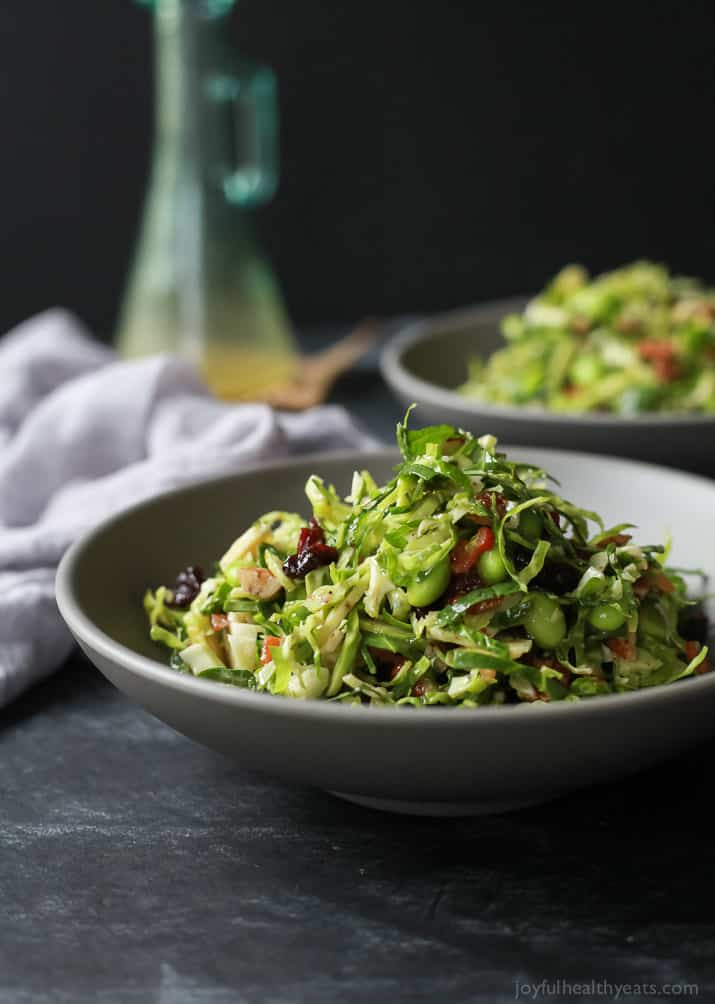 A light gluten free Autumn Kale & Shaved Brussel Sprout Salad infused with crispy bacon, edamame, and a surprise sweet fruit that compliments the dish perfectly. The ultimate side dish you need on your table this holiday season! |joyfulhealthyeats.com