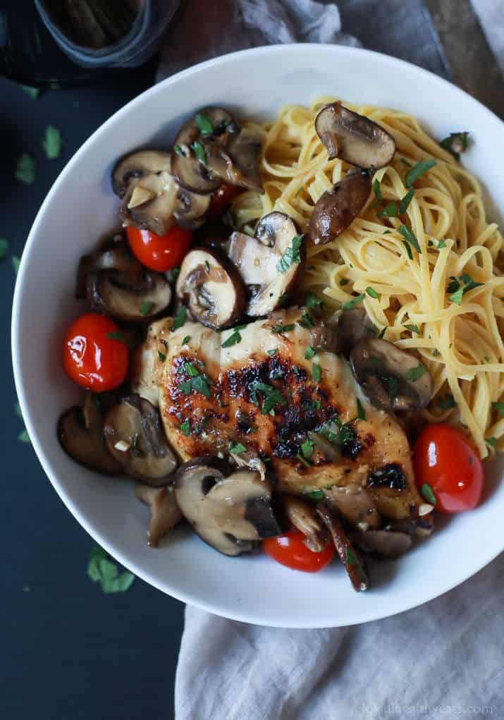 Top view of Chicken Marsala topped with Blistered Tomatoes served over pasta in a bowl