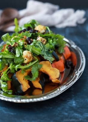 A perfect vegetarian side dish for the fall, Roasted Acorn Squash topped with a fresh Arugula Salad that's mixed with dried cherries and goat cheese balls coated with salty pistachios. De-lish!   joyfulhealthyeats.com #recipes #glutenfree #vegetarian