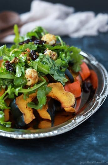 A perfect vegetarian side dish for the fall, Roasted Acorn Squash topped with a fresh Arugula Salad that's mixed with dried cherries and goat cheese balls coated with salty pistachios. De-lish! | joyfulhealthyeats.com #recipes #glutenfree #vegetarian