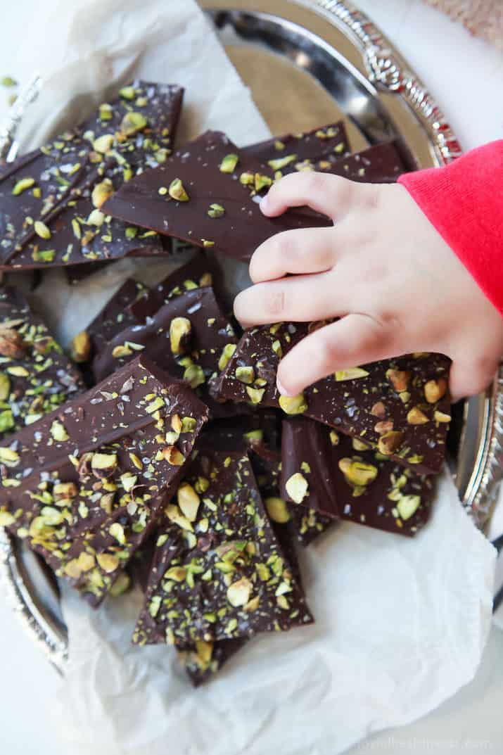 A child's hand reaching into a pile of Salted Pistachio Chocolate Bark on a platter