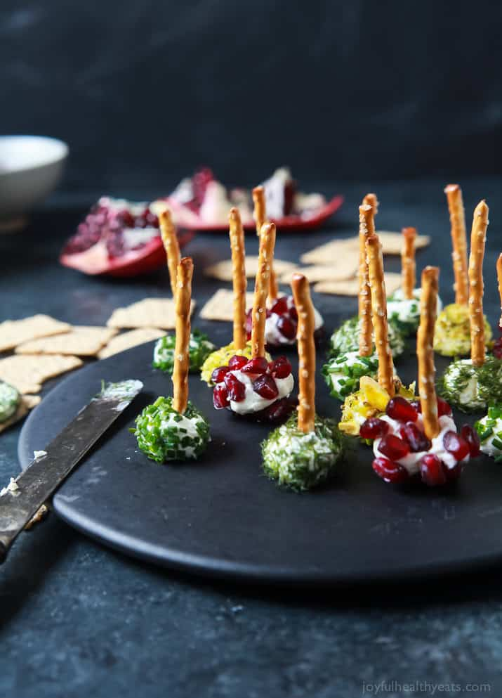 A plate of goat cheese balls coated in chives, dill, pistachio, and pomegranate with a pretzel stick on top