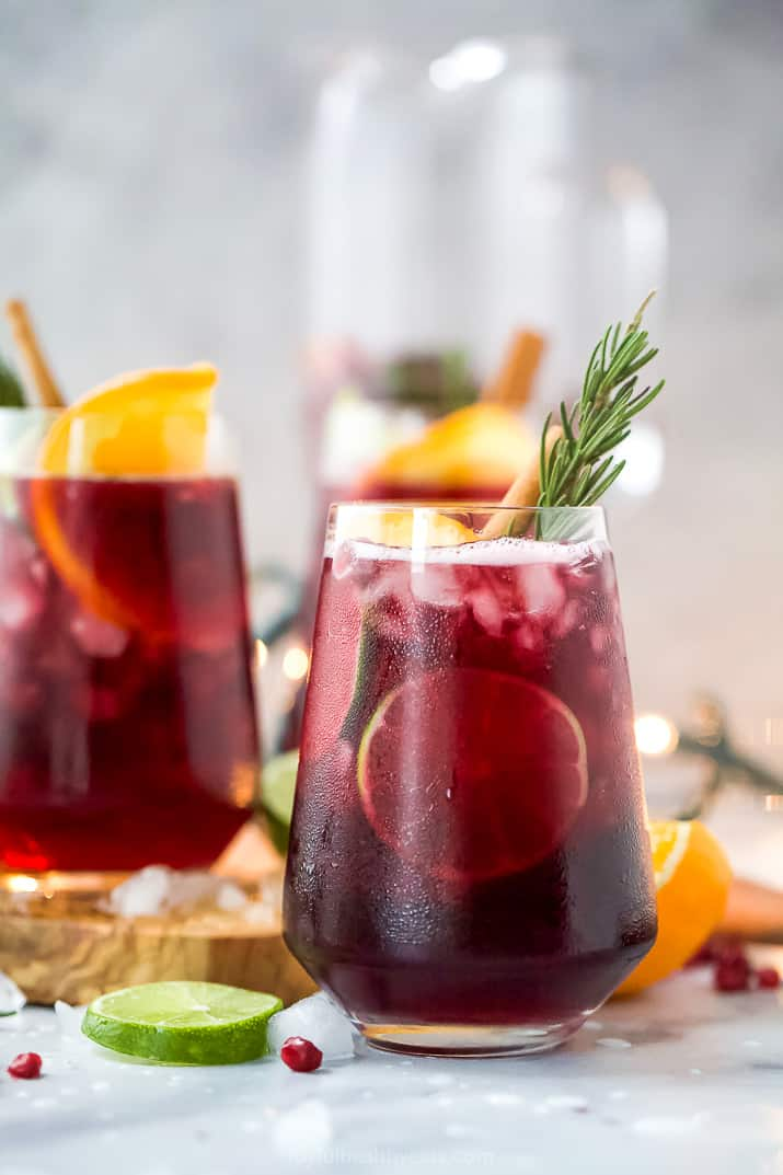 the ultimate holiday sangria recipe in a glass with garnishes