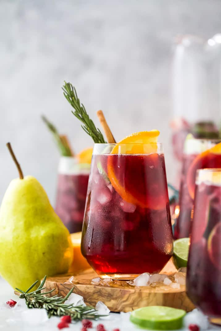 the ultimate holiday sangria recipe in a glass with ice and garnishes