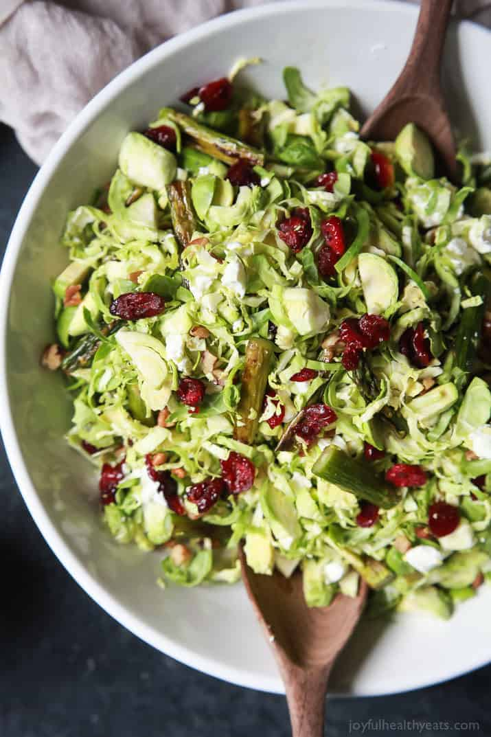 Asparagus & Brussel Sprout Salad topped with dried cranberries and Honey Dijon Dressing