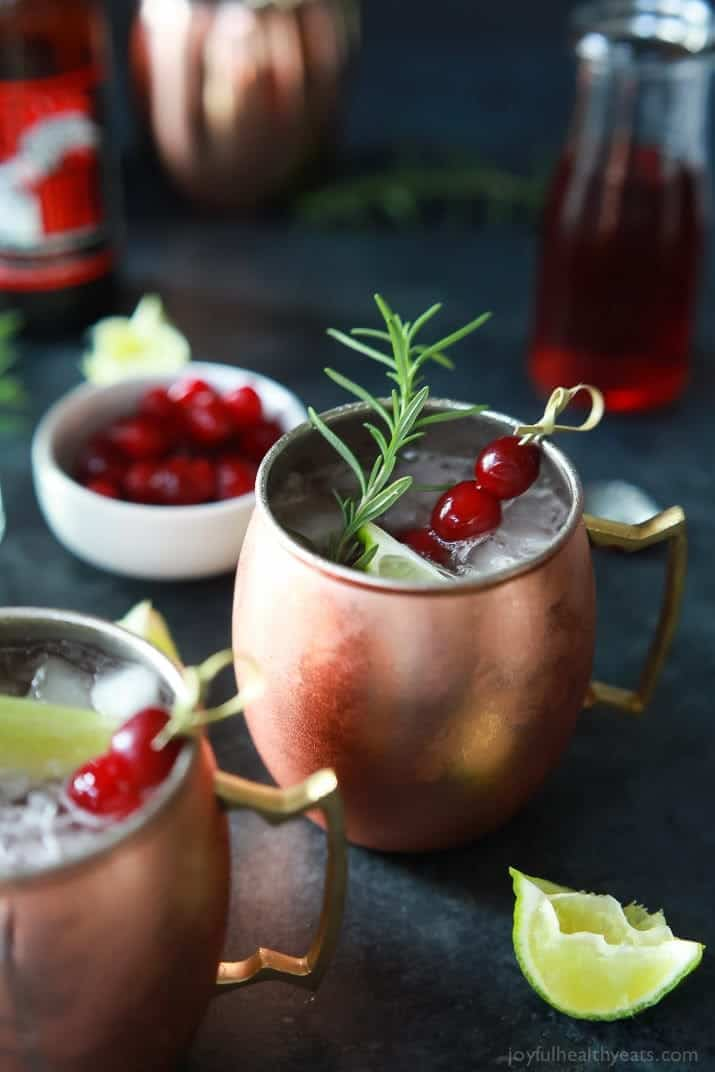 Two mugs of Cranberry Moscow Mule with Rosemary Infused Vodka