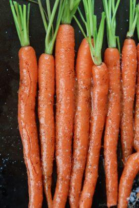 Eight Honey Mustard Glazed Carrots Lined Up on a Baking Sheet