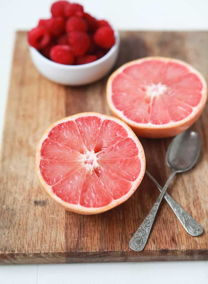 Two halves of grapefruit and a bowl of raspberries on a wooden board