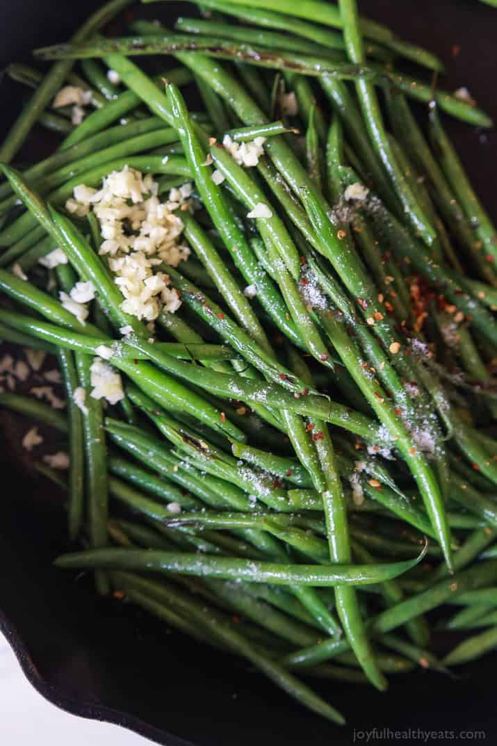 Green Beans in a Skillet Topped with Minced Garlic and Red Pepper Flakes