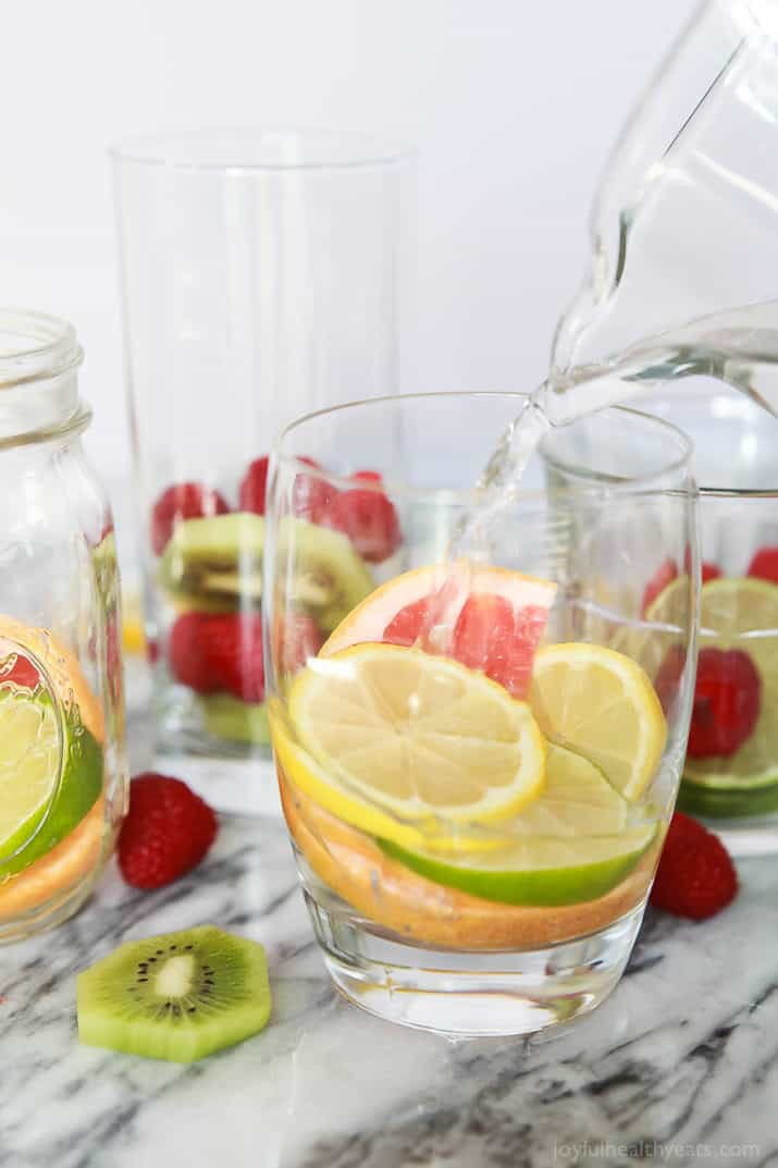 Water being added to fruit in a glass to make Fruit Infused Water