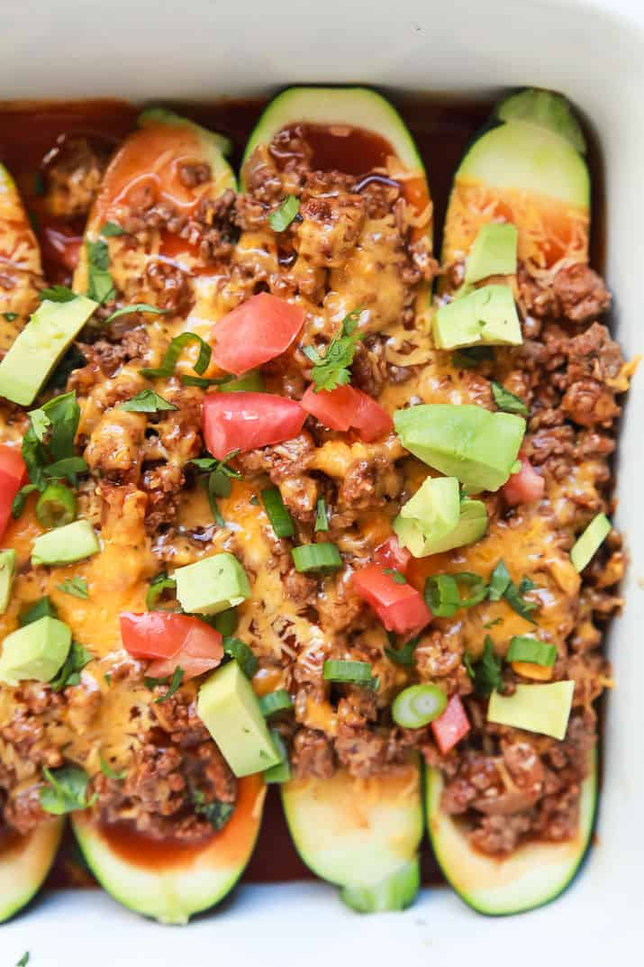 Top view of Ground Beef Enchilada Zucchini Boats in a baking dish topped with diced tomato and avocado