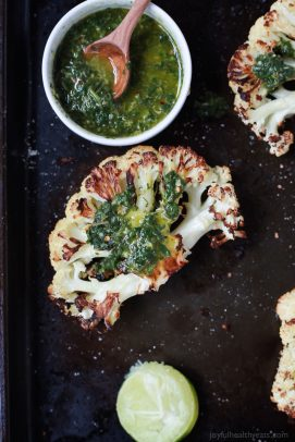 roasted cauliflower steaks with chimichurri sauce on a baking sheet