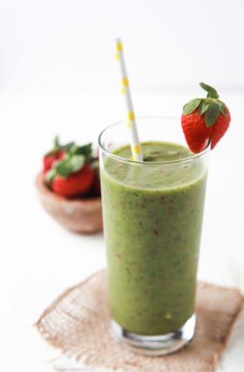 A glass of Easy Tropical Green Smoothie with a strawberry wedged onto the side of the glass and a bowl of strawberries behind it | joyfulhealthyeats.com Easy Healthy Recipes