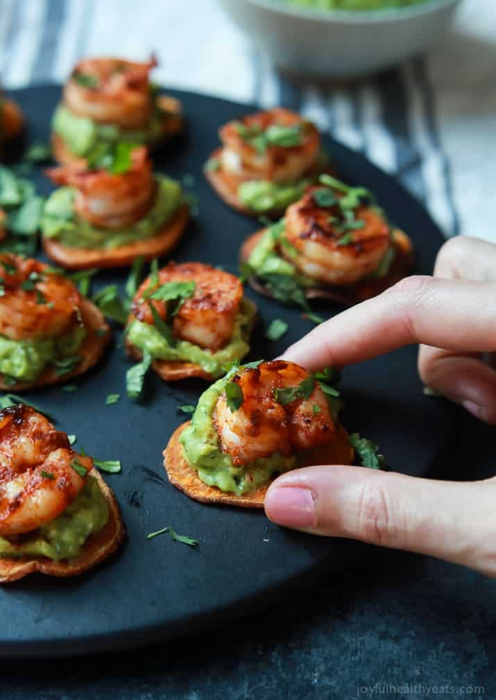 Cajun Shrimp Guacamole Bites with sweet potato slices on a round plate