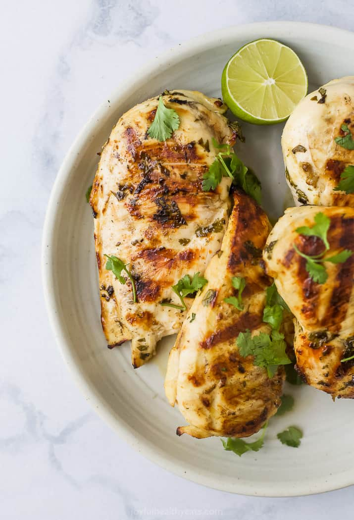 grilled cilantro lime chicken on a plate topped with fresh cilantro