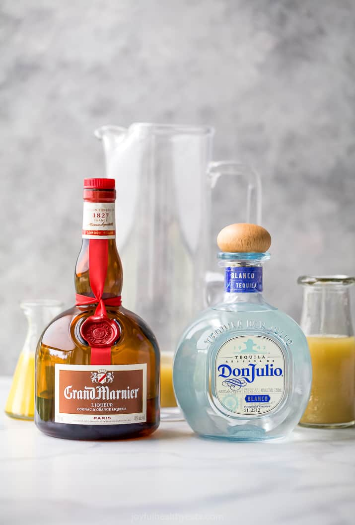 bottles of grand marnier and don julio in front of pitchers of margarita