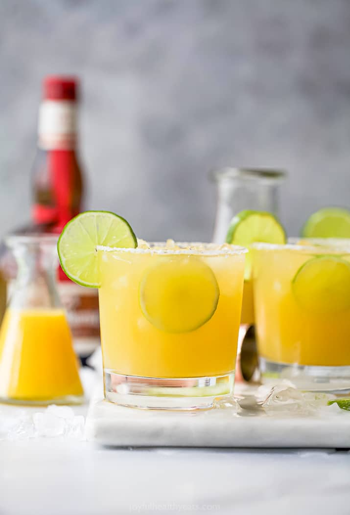 Glasses filled with margaritas and topped with lime wedges