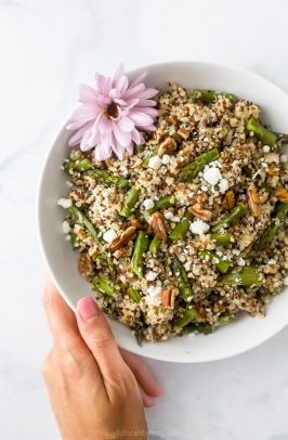 light creamy goat cheese asparagus quinoa salad in a bowl with a hand holding the bowl