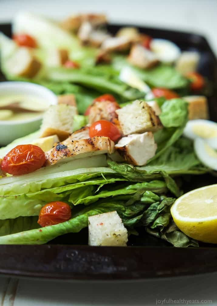 Close-up view of Grilled Chicken Caesar Salad on whole romaine leaves with grape tomatoes