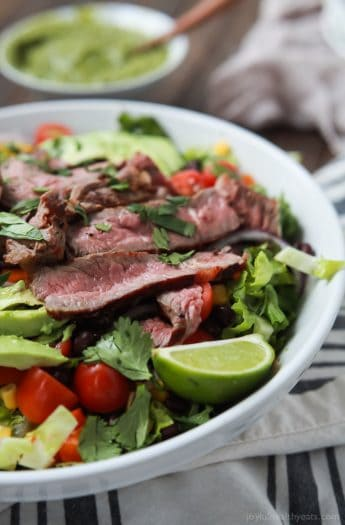 An easy healthy Southwestern Steak Salad loaded with vegetables, tender Ribeye Steak and then topped with a homemade Cilantro Avocado Dressing! Done in 15 minutes, low on calories and rivals any restaurant salad! | joyfulhealthyeats.com #glutenfree