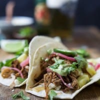 Crock Pot Pork Carnitas Tacos - the easiest pork carnitas you'll ever make with the BEST flavor from a secret ingredient. Then these tacos are topped with a creamy Cilantro Lime Avocado Crema for the ultimate bite! | joyfulhealthyeats.com