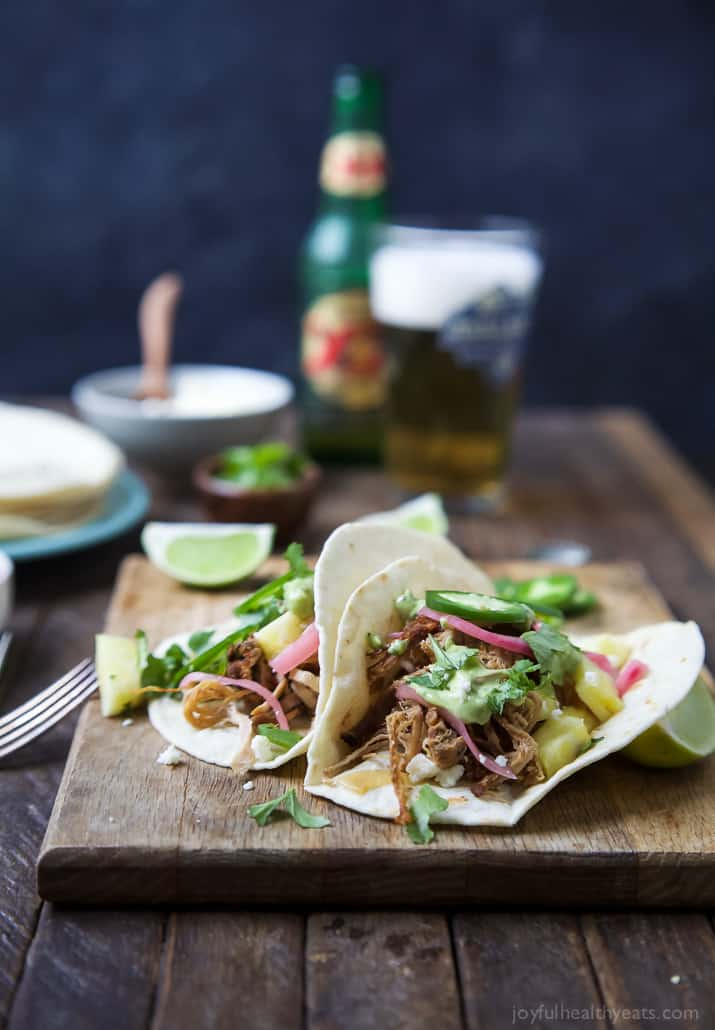 Two Pork Carnitas tacos with red onion, avocado crema and fresh cilantro