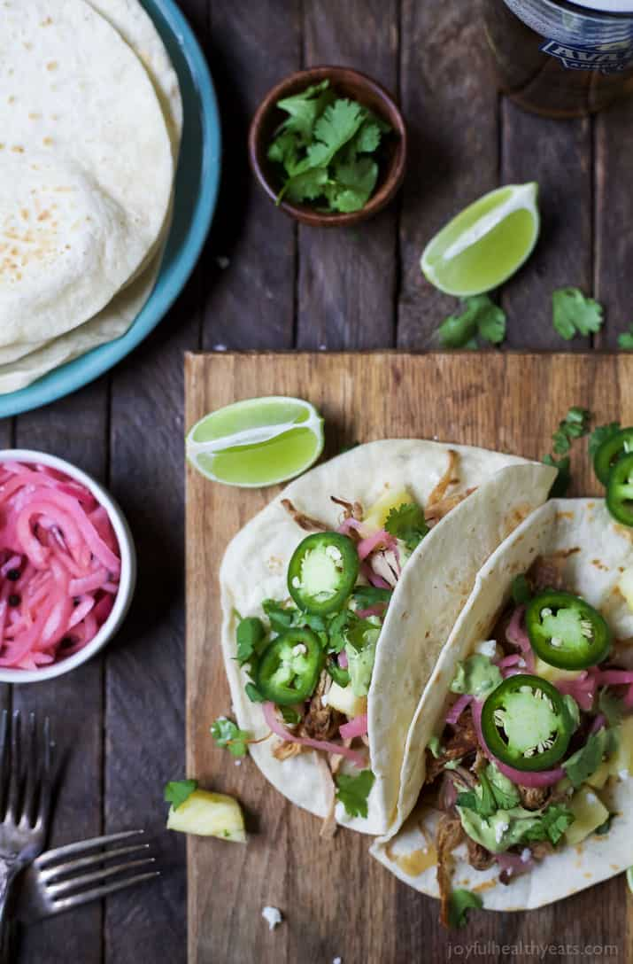 Two Pork Carnitas tacos with red onion, avocado crema and fresh cilantro and jalapeno slices