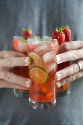 Three glasses of Strawberry Mojito being held by hands