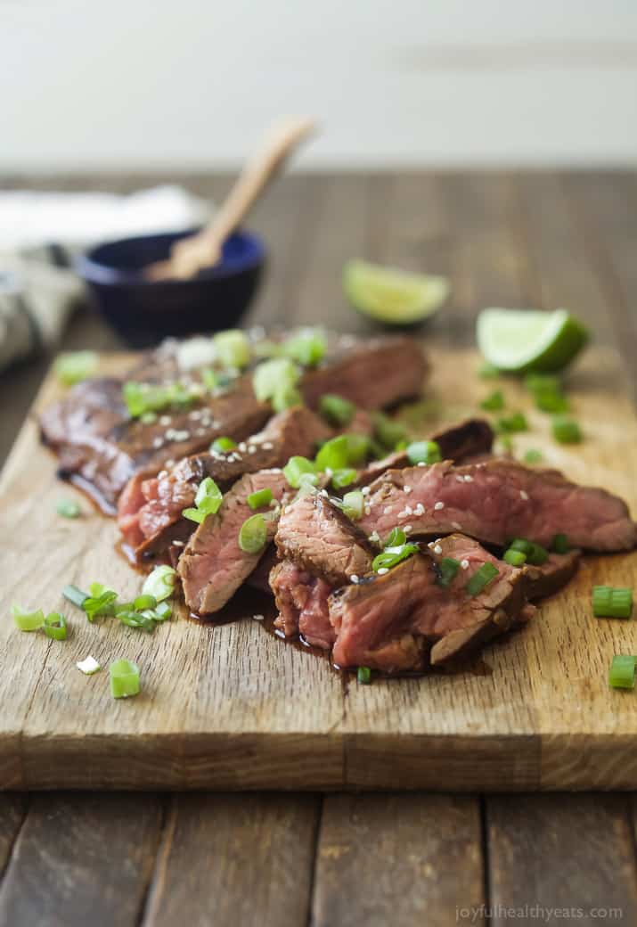 Sliced Asian Grilled Flank Steak on a cutting board with scallions