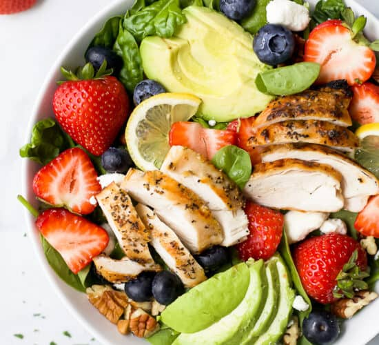 a bowl filled with best avocado strawberry salad with grilled chicken