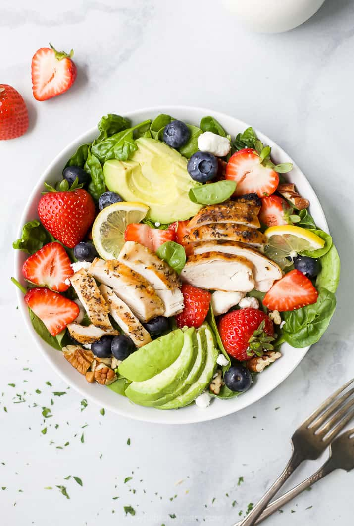 overhead photo of best avocado strawberry spinach salad with grilled chicken