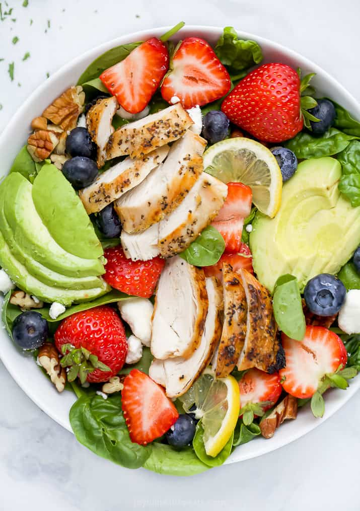 closeup of best avocado strawberry salad with grilled chicken