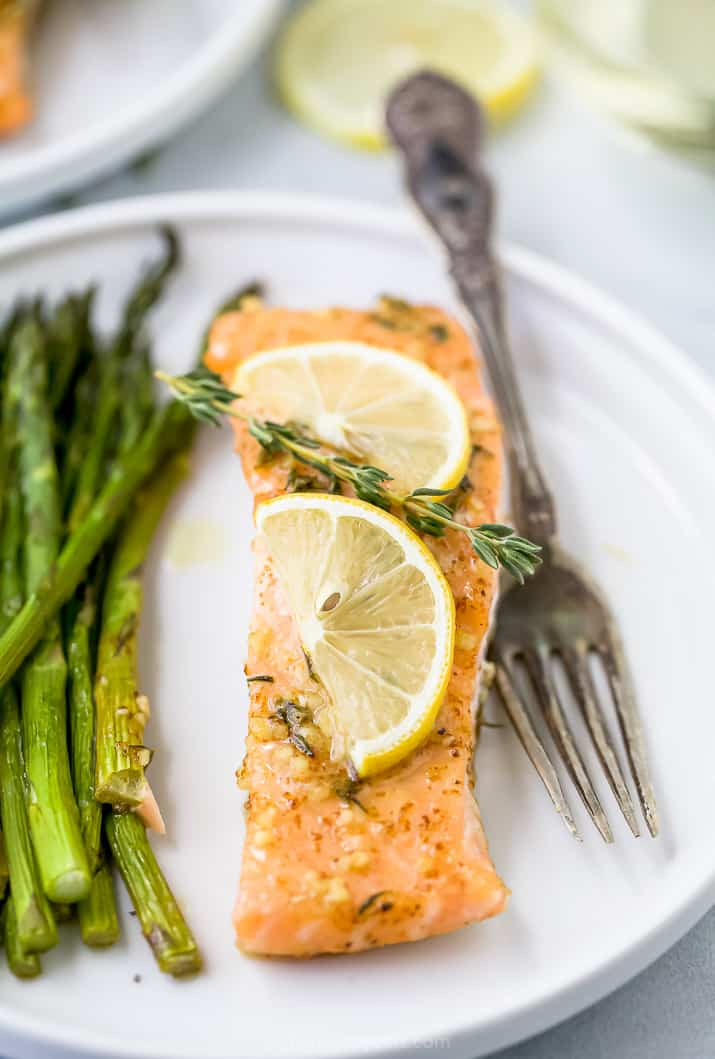 a plate with salmon topped with lemon and asparagus