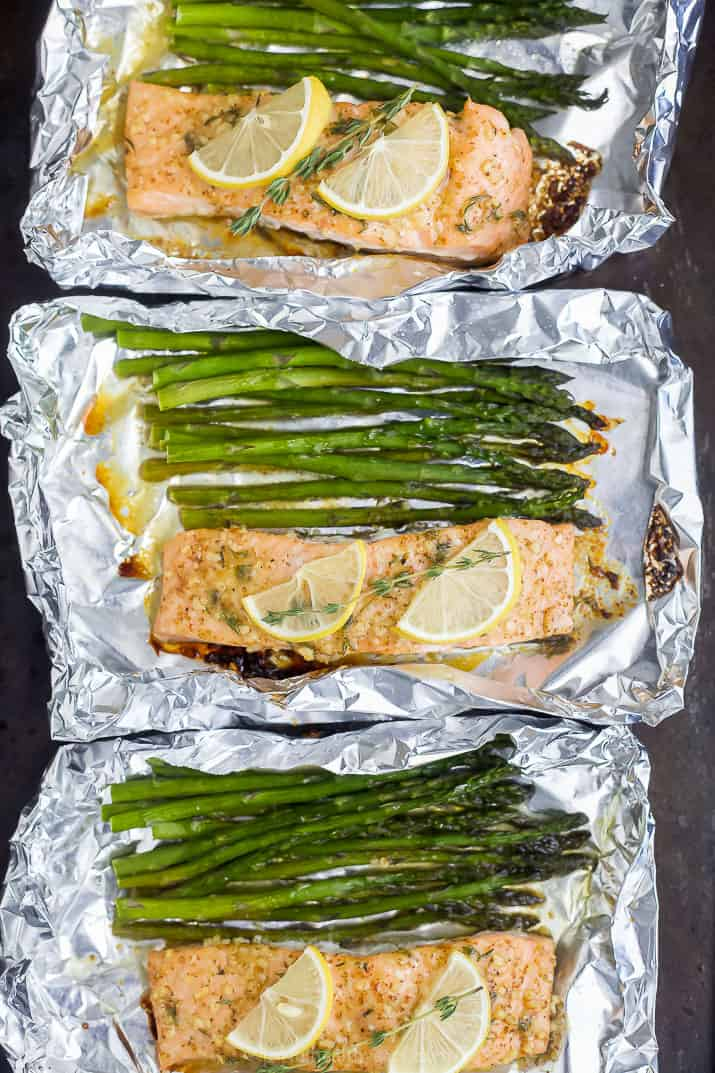 three tin foil packets with baked salmon and asparagus