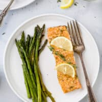 a plate with salmon topped lemon slices and thyme next to asparagus